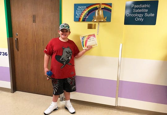 Cancer patient Leland Haley holding his certification for completing treatment